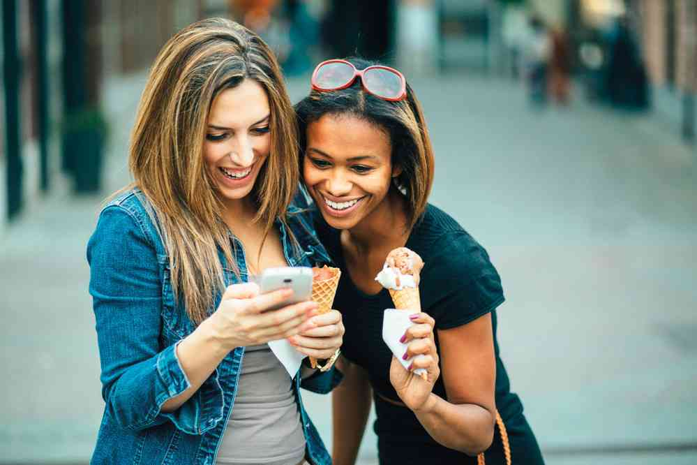 two girls looking at phone and laughing while holding ice cream cones