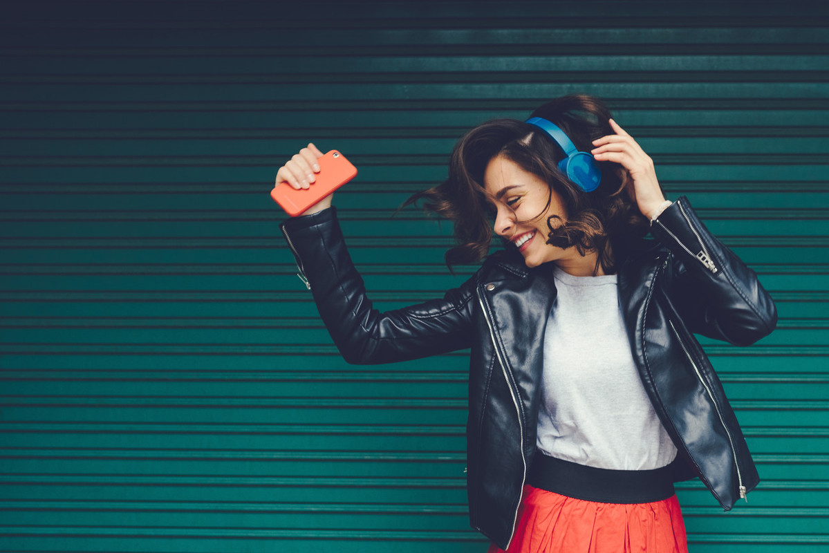 girl dancind with headphones on and phone in her hand