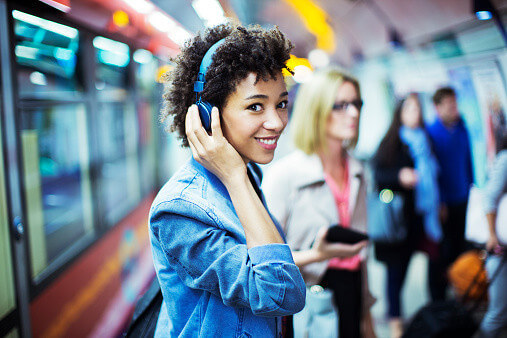 woman listening to music on headphones while commuting