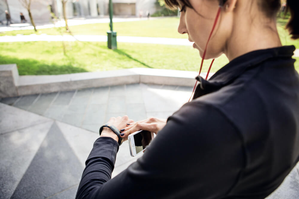 woman in workout clothes wearing headphones looking at activity tracker