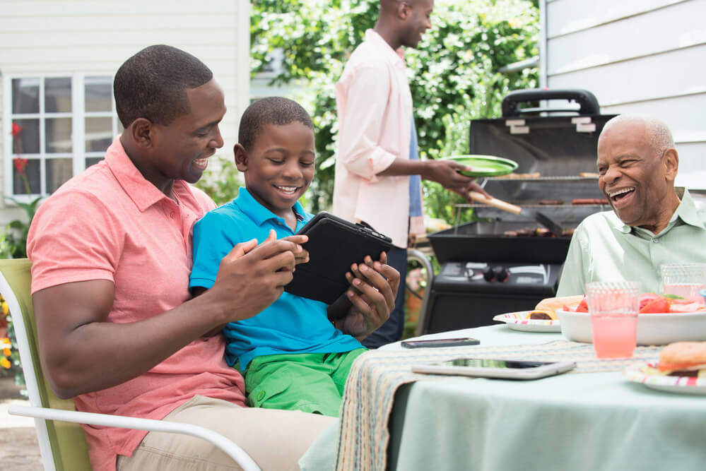 three generation family sitting on patio looking at tablet while cooking out