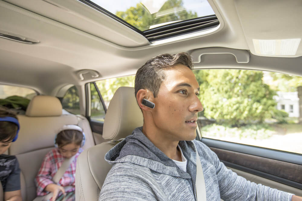 man driving in car with bluetooth headset and kids in the backseat