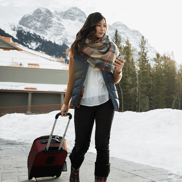 Young woman holding phone with carry-on luggage in a snowy mountain scene.