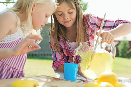 two young girls pouring lemonade