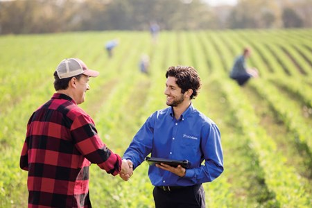 US Cellular representative shaking hands with farmer outside in field