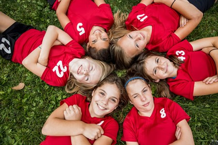 girls sport teammates laying in grass in a circle looking up