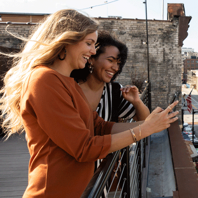 Two friends looking at phone. U.S. Cellular Refer A Friend and Get $100.