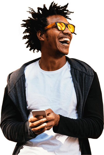 Young man laughing, wearing sunglasses and holding a cell phone.