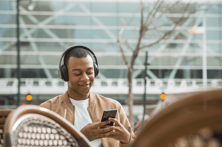Man sitting outside wearing headphones and looking at mobile device and smiling